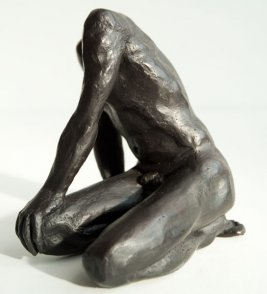frontal sinister lateral view of a sculpture of a male nude sitting on his knees