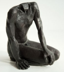dexter lateral frontal view of a sculpture of a male nude sitting on his knees