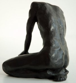 sinister lateral dorsal view of a sculpture of a male nude sitting on his knees