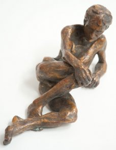 caudal view of bronze sculpture of a male nude leaning on his ellbow