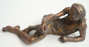 frontal view of bronze sculpture of a male nude leaning on his ellbow