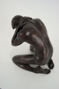 cranial lateral dorsal view of a bronze sculpture of a male nude kneeling down