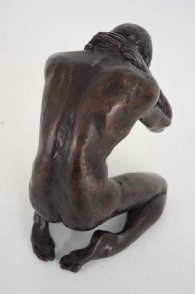 cranial dorsal lateral view of a bronze sculpture of a male nude kneeling down