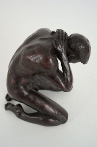 cranial lateral view of a bronze sculpture of a male nude kneeling down