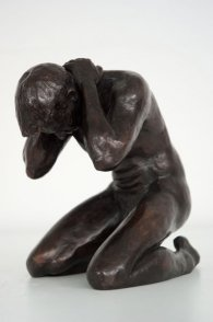 lateral frontal view of bronze sculpture of a male nude kneeling down