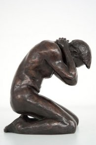 lateral view of a bronze sculpture of a male nude kneeling down