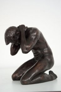 lateral frontal view of a bronze sculpture of a male nude kneeling down