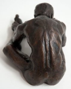 dorsal view of a bronze sculpture of a male nude sitting with his head on his knee