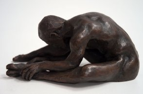 sinister lateral view of a bronze sculpture of a male nude sitting with his head on his knee