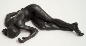 cranial frontal view of bronze sculpture of a female nude lying down