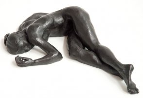 frontal view of bronze sculpture of a female nude lying down