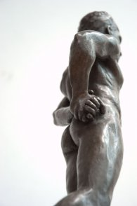 caudal dorsal lateral view of bronze sculpture of male nude standing figure