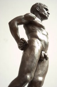 caudal lateral frontal view of bronze sculpture of male nude standing figure