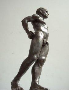 caudal lateral frontal view of bronze sculpture of standing male nude figure