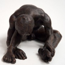 bronze sculpture of a male nude sitting with his head resting on his knee
